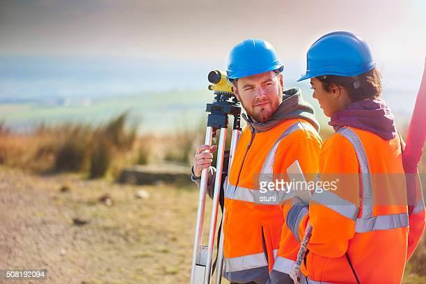 two construction site surveyors
