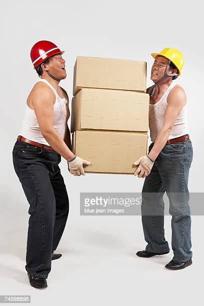 Two construction workers carrying boxes