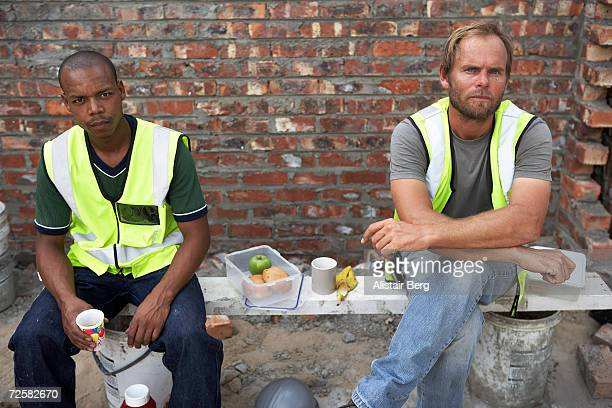 Two construction workers eating lunch on site