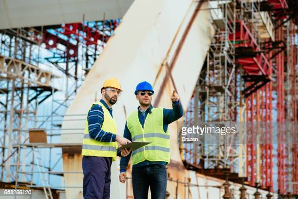 Two construction workers - engineers on construction site agreeing upon next building phase