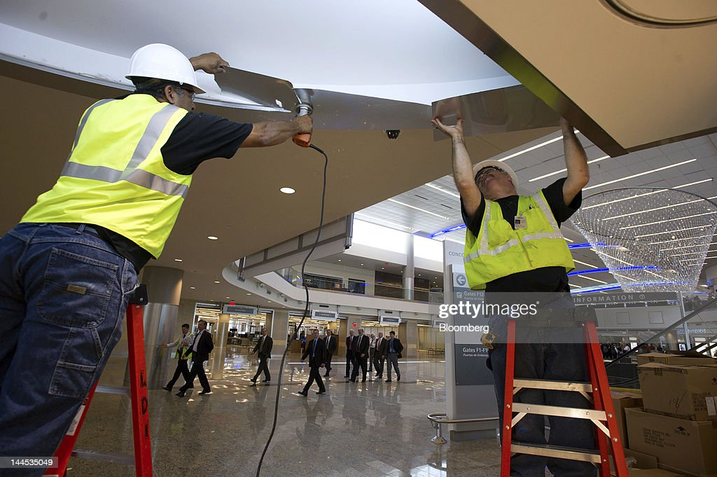 Two construction workers finish the Coach and Armani storefronts at the Maynard H Jackson Jr International Terminal at HartsfieldJackson...