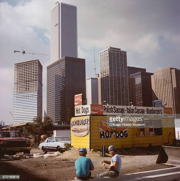 Two construction workers outside a hot dog stand Chicago Illinois 1987 View of the city in the background