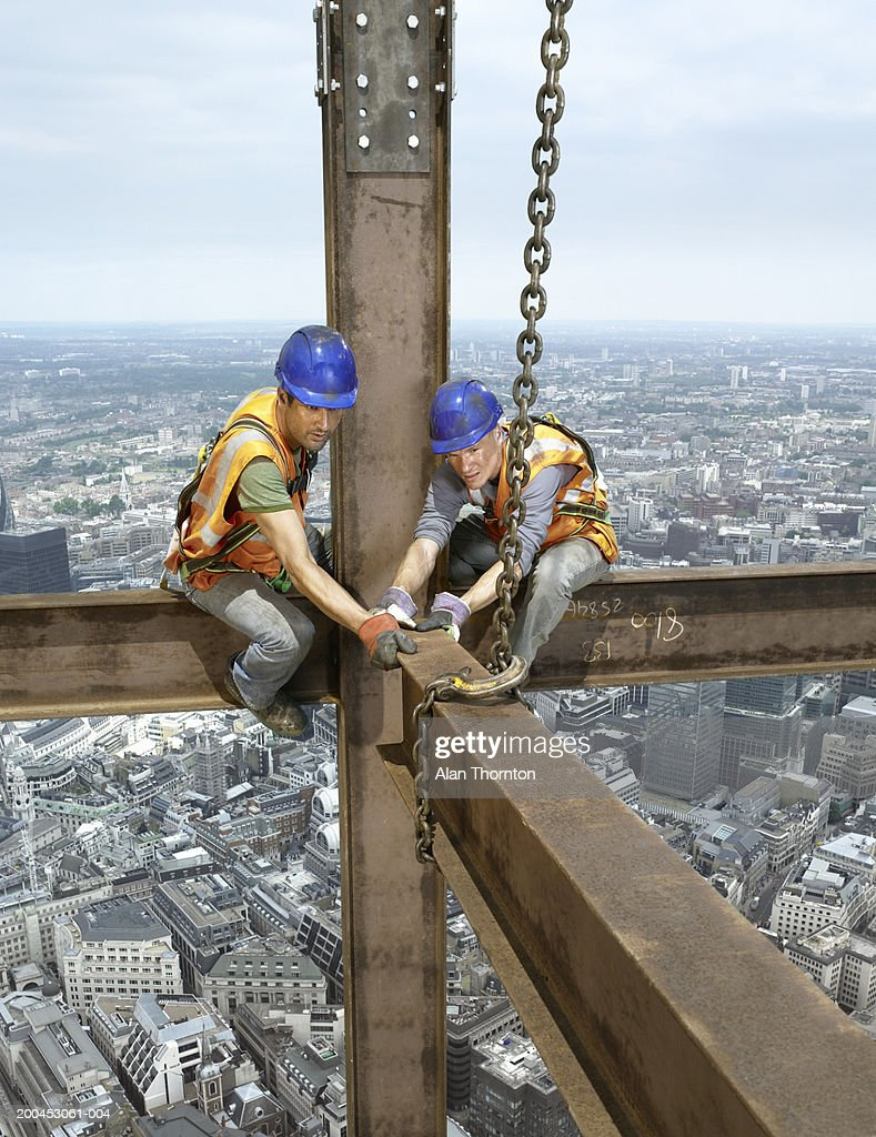 Two construction workers sitting on beam above cityscape
