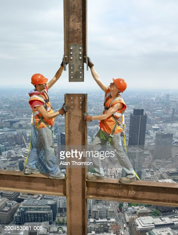 Two construction workers standing on beam above cityscape : Stock Photo