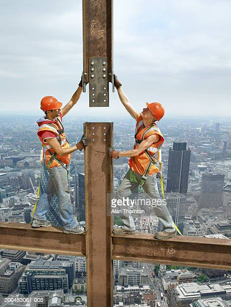 Two construction workers standing on beam above cityscape