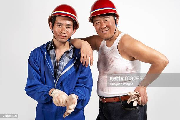Two construction workers standing side by side looking content