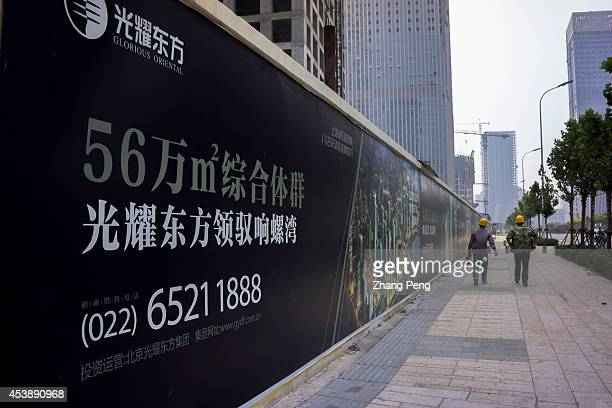 Two construction workers walk beside a real estate advertising and a group of unfinished buildings in Xiangluo Bay Yujiapu Xiangluowan a new biggest...