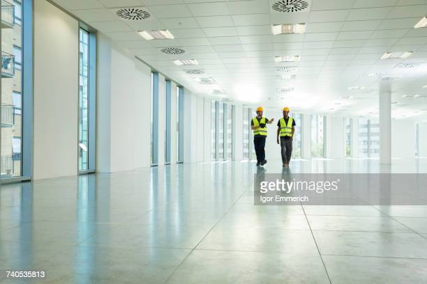 Two construction workers walking through empty office space