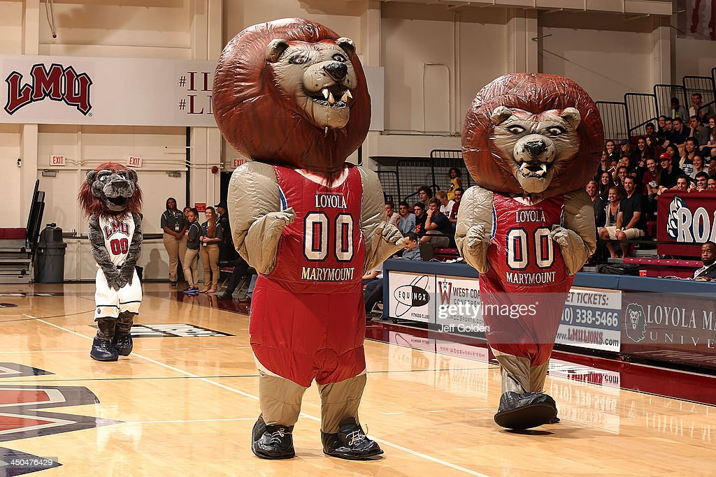 Two contestants dressed in inflatable mascot costumes race on the court as the Loyola Marymount Lions mascot Iggy the Lion watches during a halftime promotion in the exhibition game against the Cal Lutheran Kingsmen at Gersten Pavilion on November 2, 2013 in Los Angeles, California. Loyola Marymount won 96-64.
