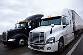 Two contrasting shiny modern black and white big rigs semi trucks with a trailers and a high sleeper cab for truckers relaxing on truck stop move side by side along the interstate highway carrying com