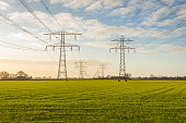 Backlit image of two converging high voltage lines in a rural Dutch landscape in the fall season.