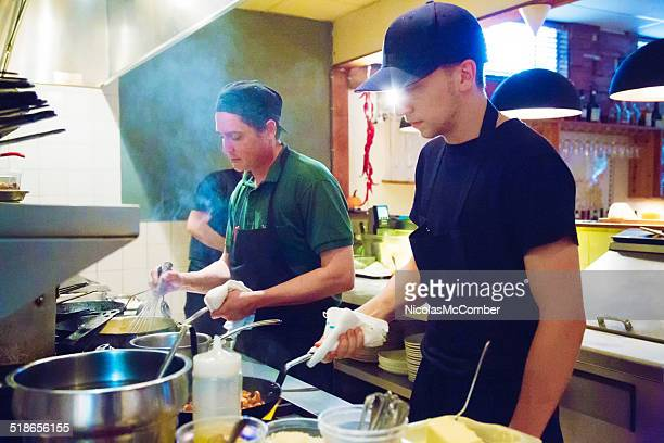 Two cooks at work during service in small restaurant kitchen