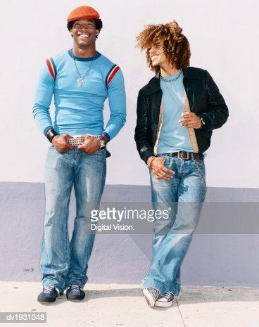 Two Cool Twentysomething Men Wearing Jeans Leaning on a Wall : Stockfoto
