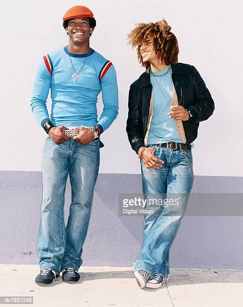 Two Cool Twentysomething Men Wearing Jeans Leaning on a Wall