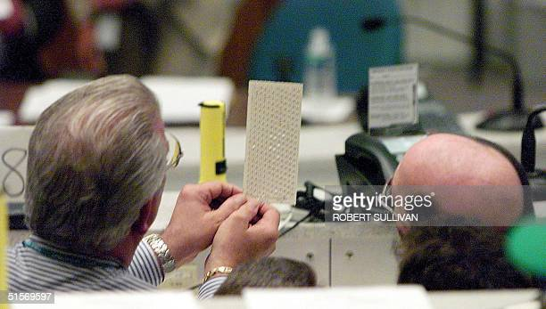 Two county election counters look at a ballot after the vote recount was reinitiated inside the Emergency Operations Center 16 November 2000 in West...