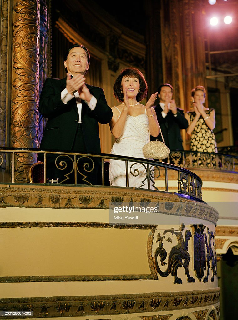 Two couples applauding in balcony of theater