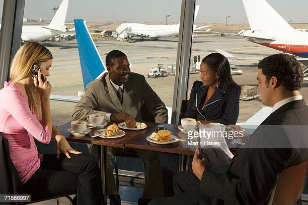 Two Couples at an Airport Restaurant Waiting for Flights