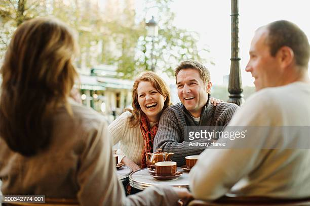 Two couples at outdoor cafe (focus on couple laughing in background)