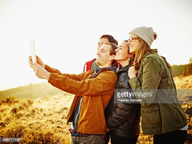 Two couples at sunset taking digital self portrait