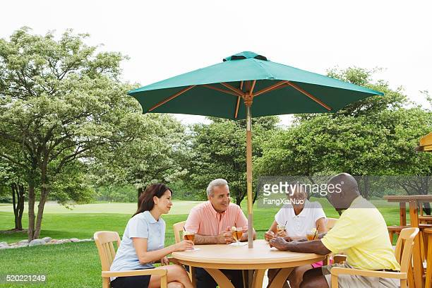 Two couples drinking at table on lawn