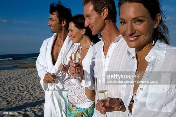 Two couples drinking champagne on beachsmiling
