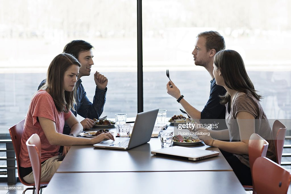 Two couples eating computers on table. : Stock Photo