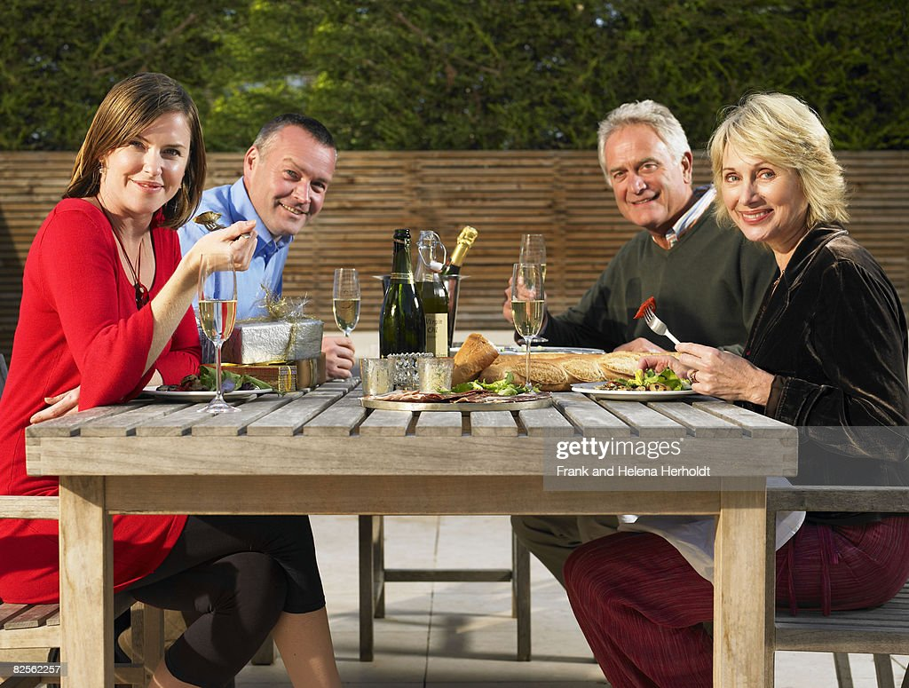 Two couples eating outdoors