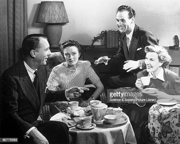 Two couples enjoying afternoon tea in a sitting room The woman on the left looks as though she is worried about something