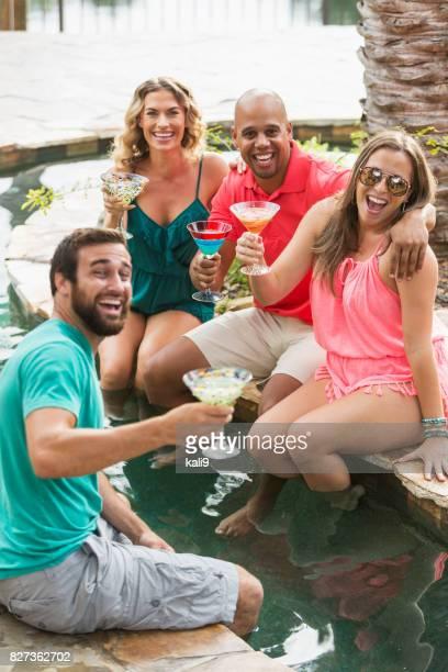 Two couples enjoying drinks by resort swimming pool