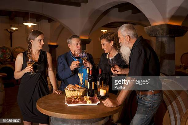 Two Couples Enjoying Food and Red Wine, Cellar in Europe