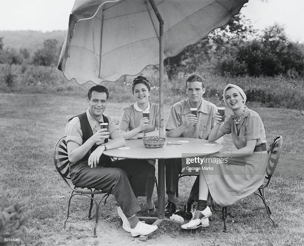 Two couples having beer at garden table, (B&W), portrait : Stock Photo