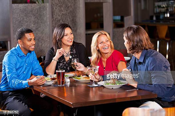 Two couples having dinner at restaurant