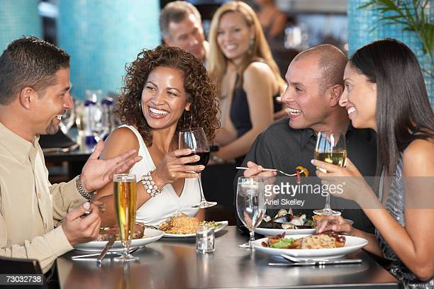 Two couples having dinner in restaurant, laughing