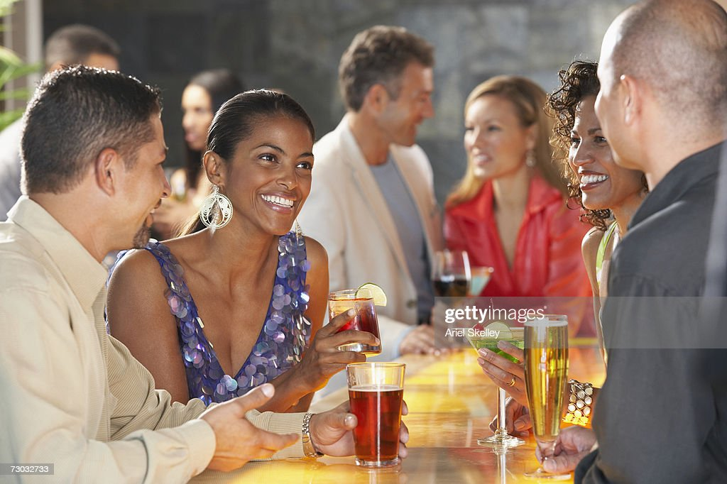 Two couples having drinks in bar, smiling : Stock Photo