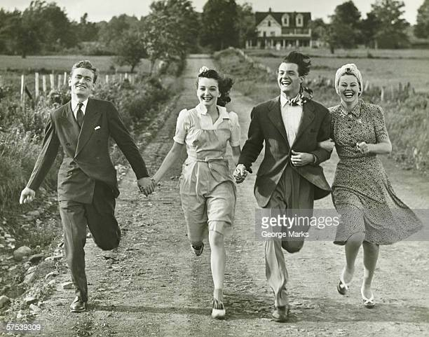 Two couples holding hands, running on footpath, (B&W)