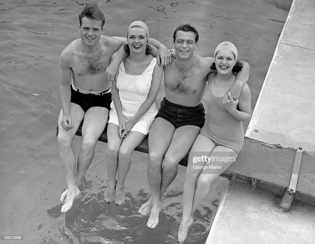 Two couples in bathing suits sitting on diving boa : Stock Photo