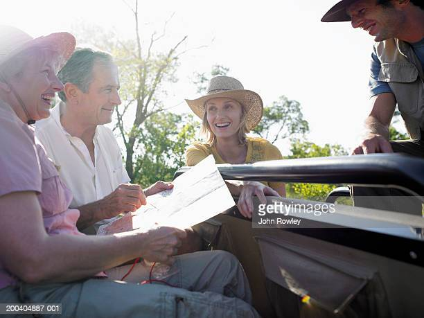 Two couples in jeep, one holding map, smiling