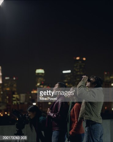 Two couples on rooftop, looking at night sky : Stock Photo