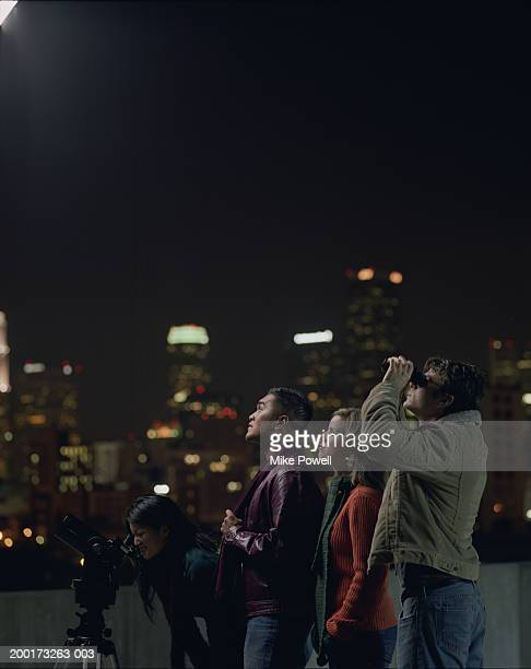 Two couples on rooftop, looking at night sky