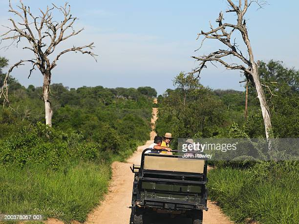 Two couples on safari sitting in 4x4 on track