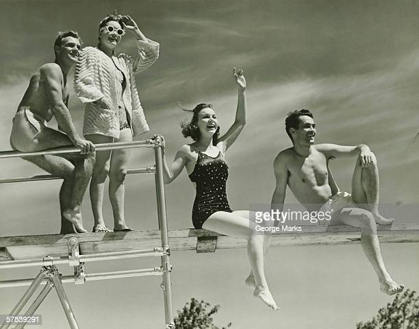 Two couples on springboard, (B&W), low angle view