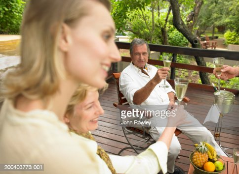Two couples proposing toast on balcony : Foto stock