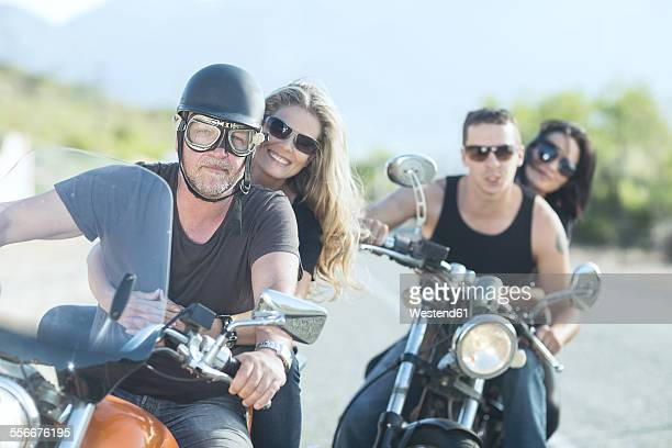 Two couples riding on motorcycles