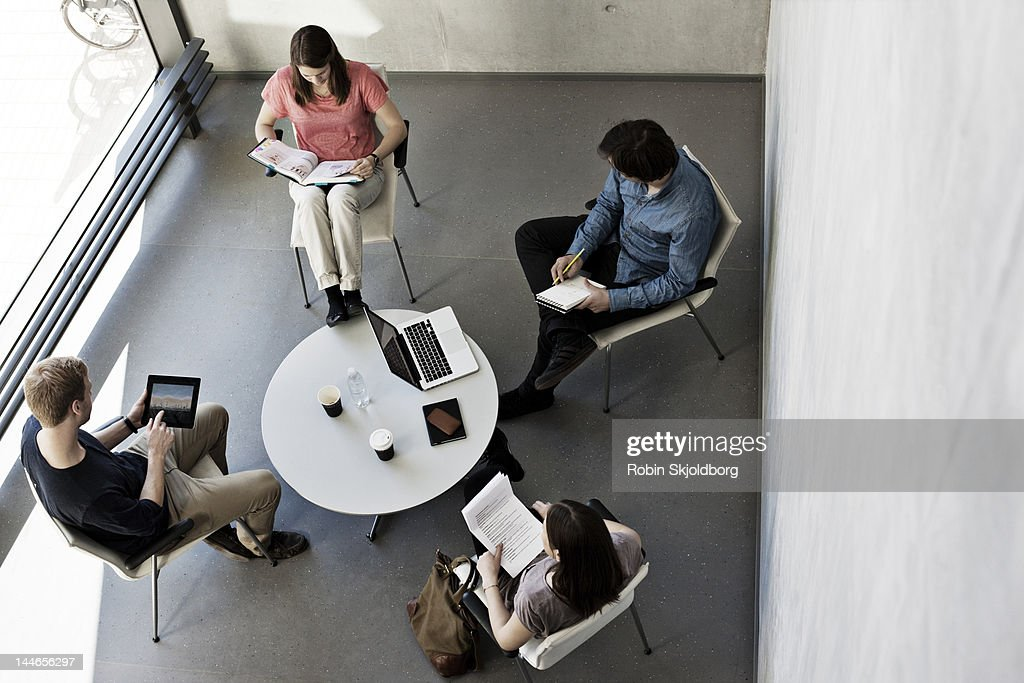 Two couples sitting around table reading. : Stock Photo