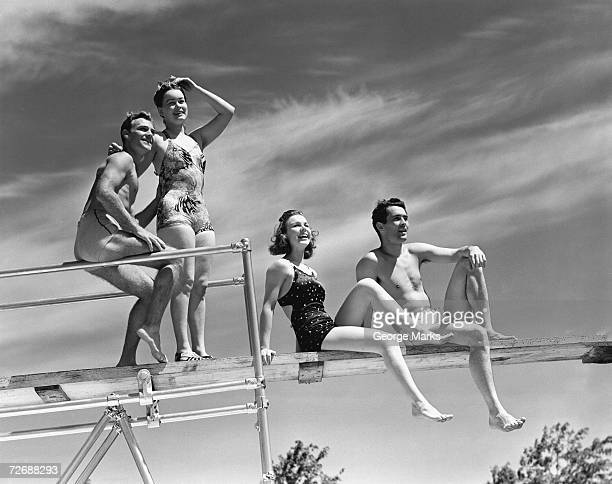 Two couples sitting on springboard, (B&W), low angle view