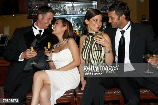 Two couples sitting on stools in bar, three quarter length : Stock Photo