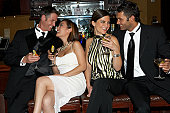Two couples sitting on stools in bar, three quarter length