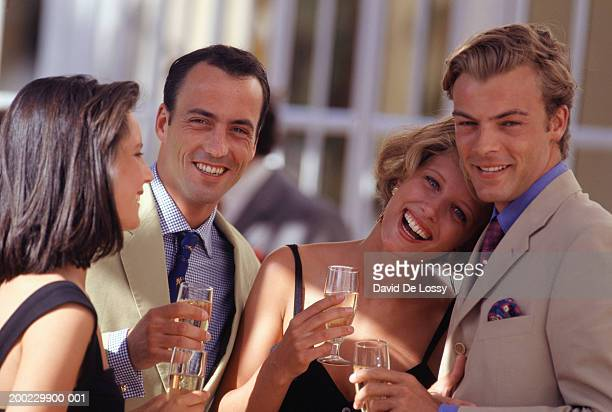 Two couples standing with glasses of champagne, outdoors