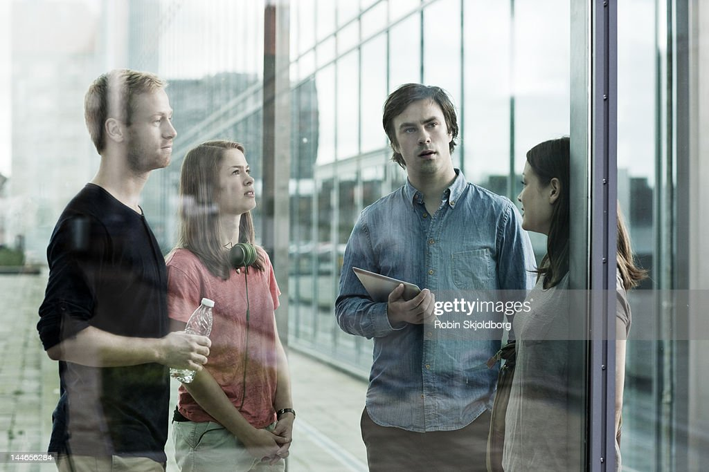 Two couples talking behind glass. : Stock Photo