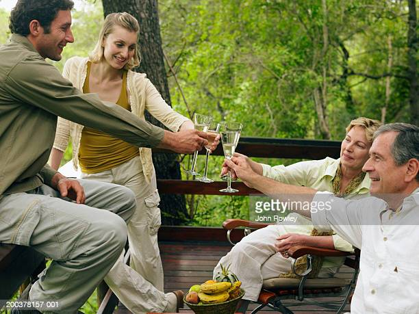 Two couples toasting each other with drinks on balcony, smiling